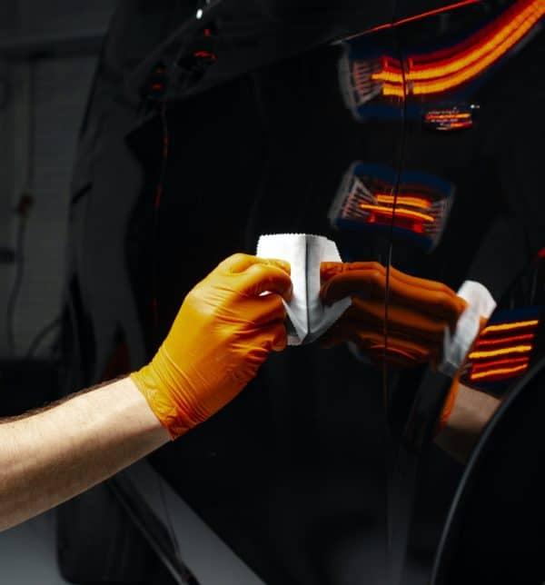 Car polish wax worker hands polishing car
